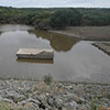 Principal spillway inlet & flood pool of watershed dam in Hays County four days after Oct. flooding.