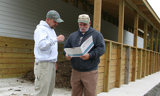 NRCS soil conservationist meets with beginning farmer Frank Robinson to review management practices on his beginning poultry farm.
