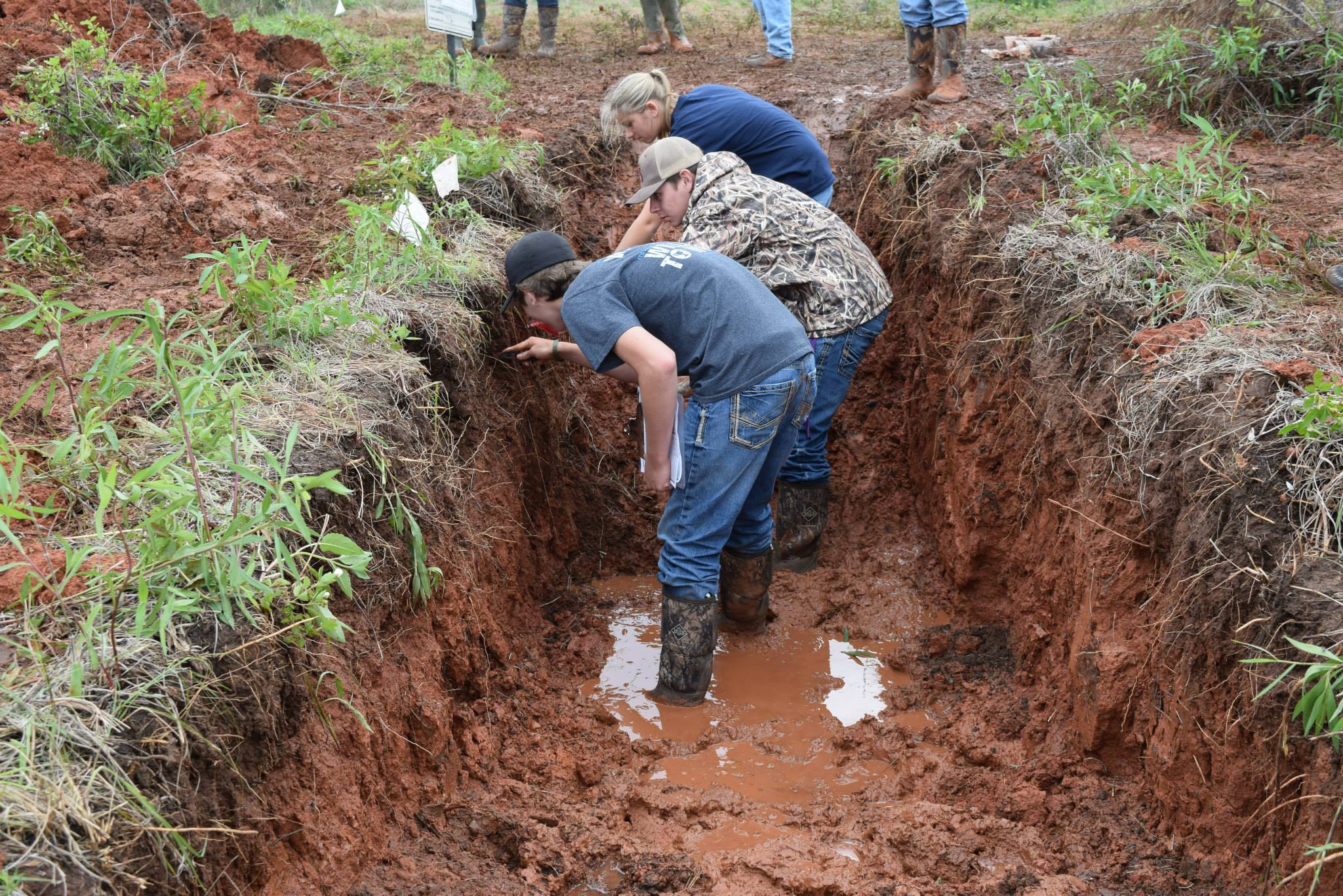 Land judging contestants in a muddy soil pit.
