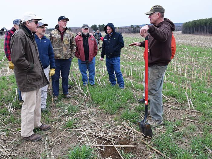 Fourth-generation Maine farmer Bob Fogler (right) talks with fellow producers, soil scientists and agricultural experts during a Spring Cover Crop Walk on his farm in Exeter, Maine, April 26, 2016. During the event - sponsored by the University of Maine Cooperative Extension and the Natural Resources Conservation Service - Fogler showed how cover crops and no-tilling farming have benefitted the soil on his dairy farm in central Maine. Photo by Thomas Kielbasa