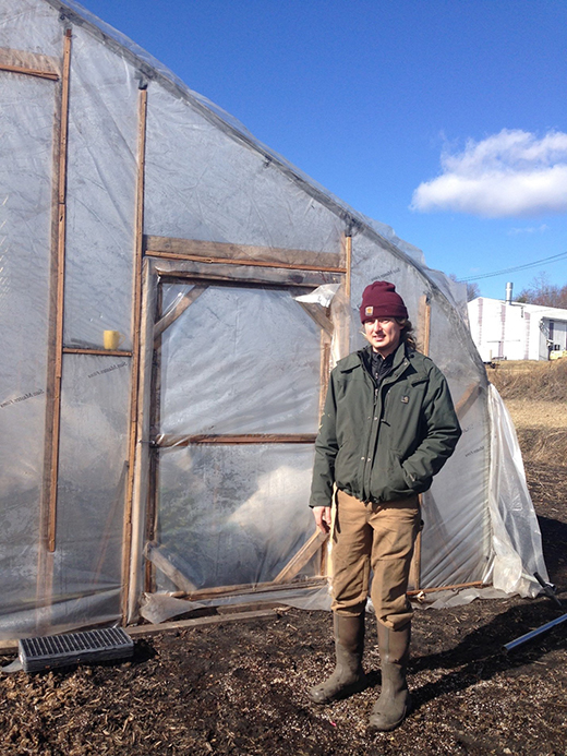 Travis Jones, Verdant Common Growers, in front of his NRCS-supported seasonal high tunnel in the black dirt region of New York. The high tunnel enables Travis to grow year-round.