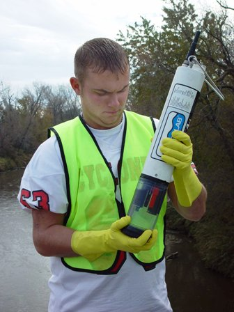 An Earth Team volunteer inspecting water sample probe