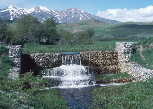 Beautiful image of mountains in the background and stone grade control structure with water flowing