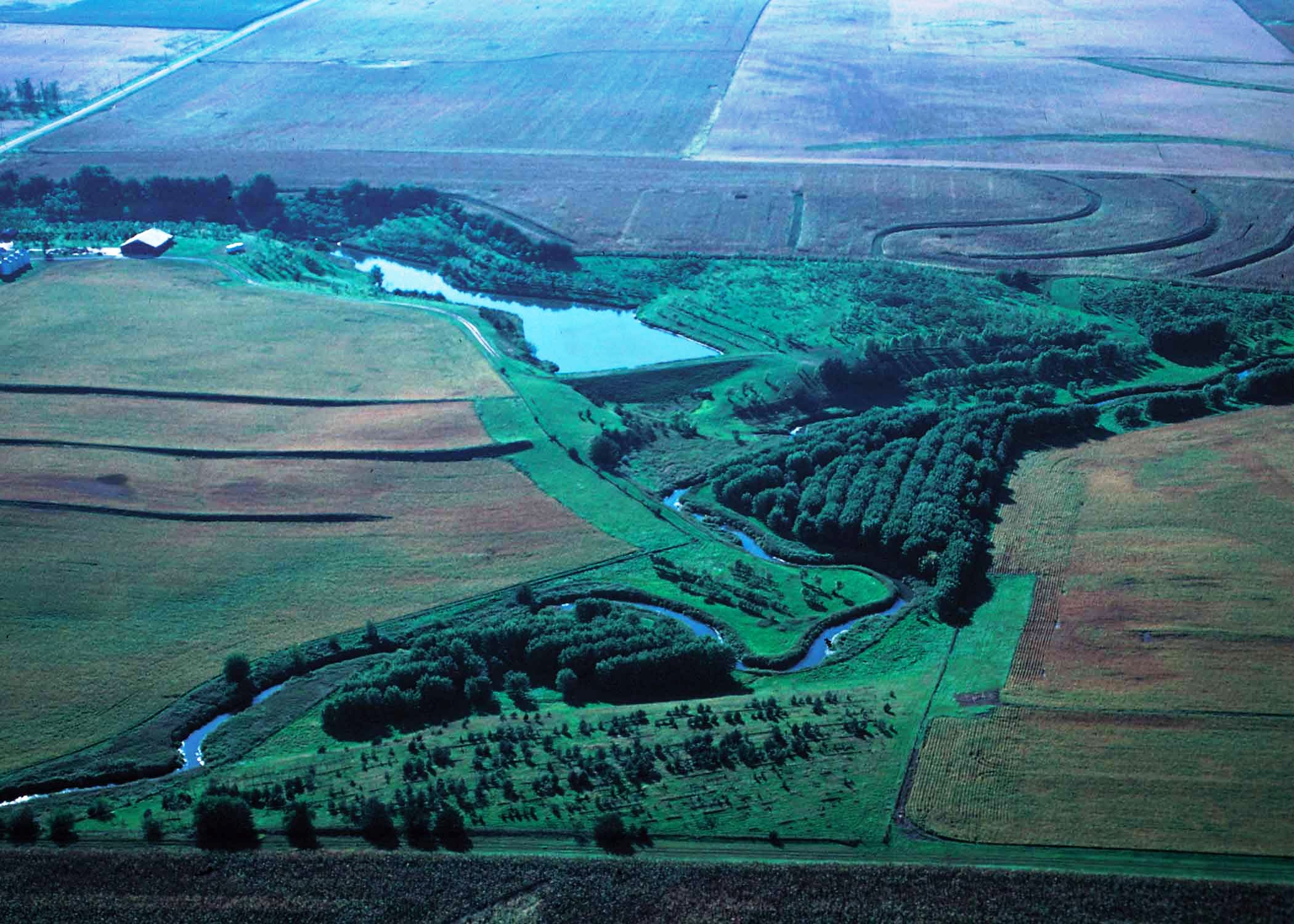 Oblique aerial view of a small watershed flood prevention structiure with green fields.