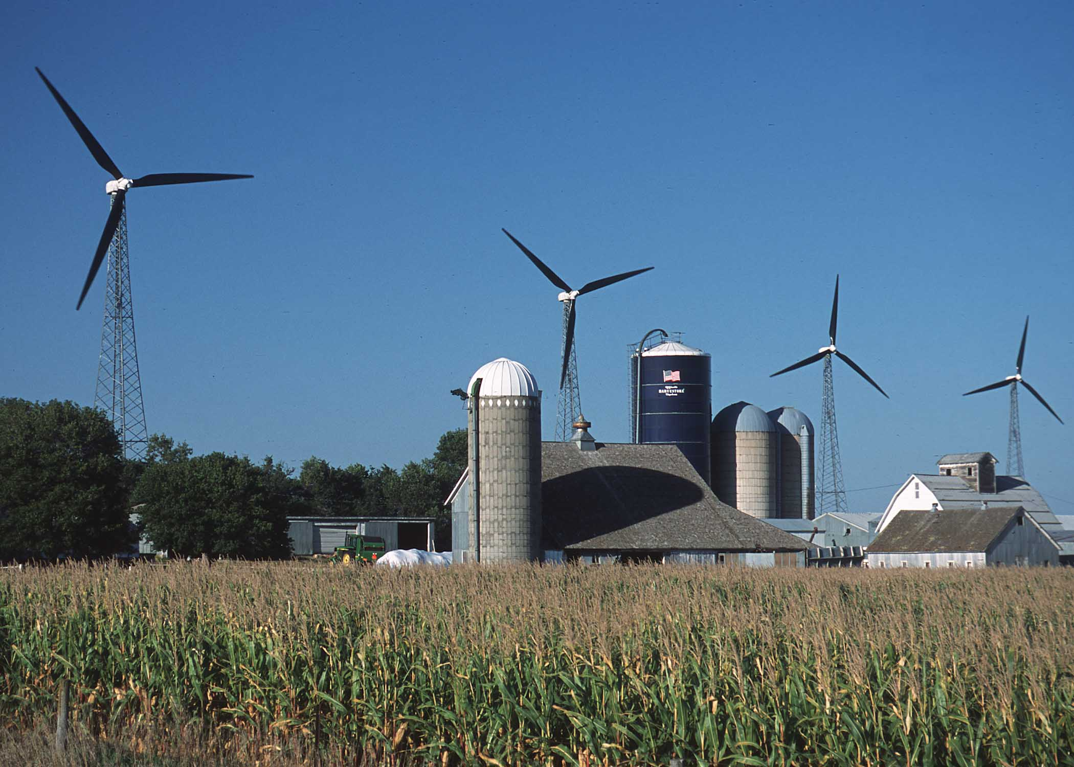 Picture of silo, green fields, with several modern wind generators in background, blue sky.