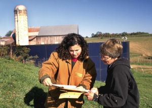 Landowner and NRCS conservationist looking at soil survey report in front of barn.