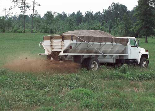 Large truck rolling through cropfield, dispensing nutrients from the back.