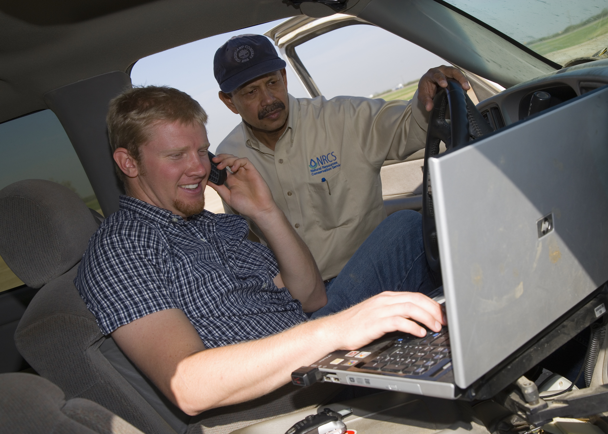 NRCS employee in car showing computer screen to farmer