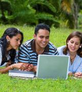 Two Hispanic girls and a boy lying in a field, looking at a laptop