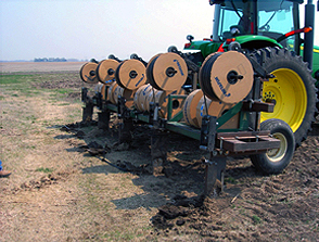 A tractor knifes in the dripline that delivers irrigation