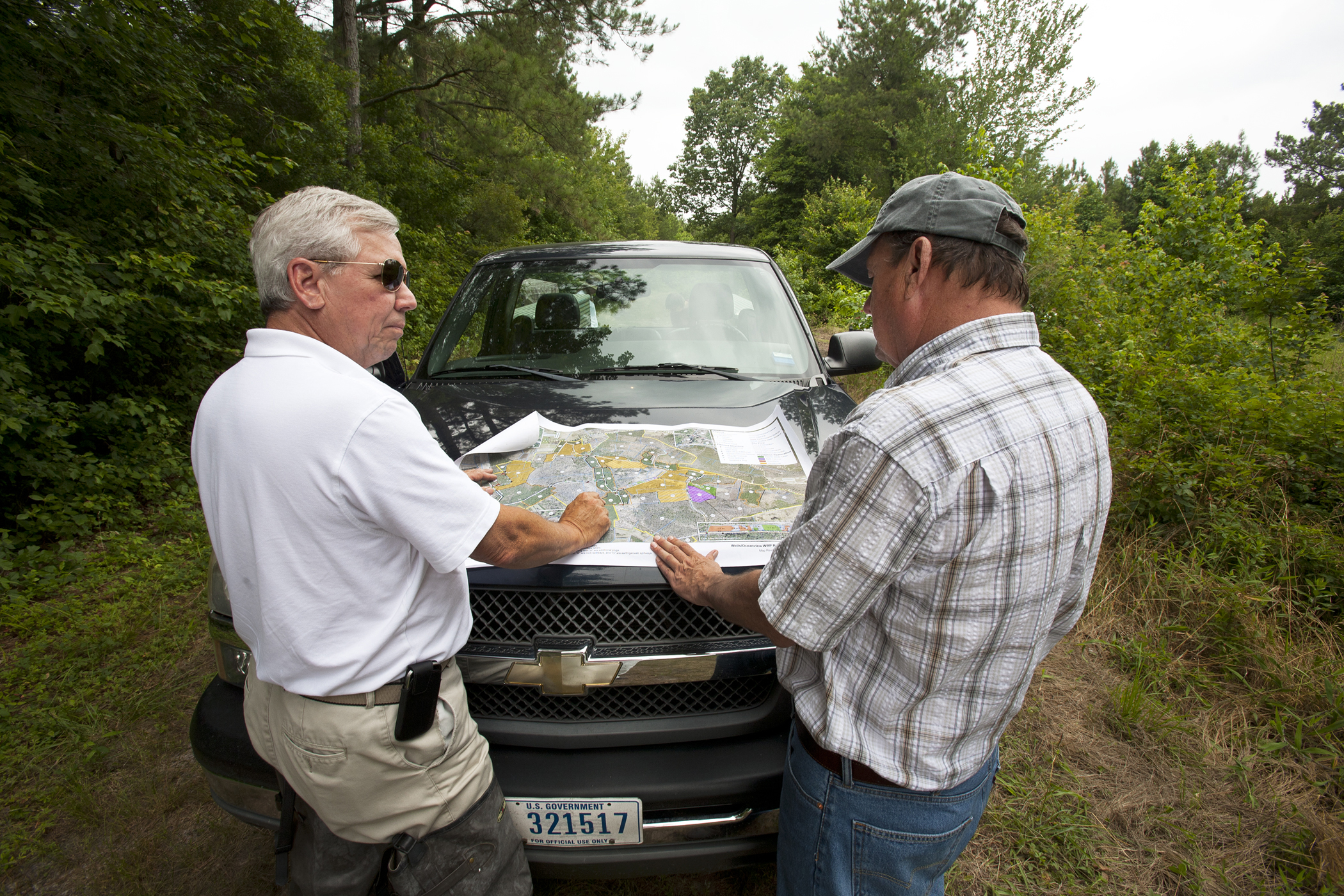 District Conservationist Nelson Brice and Kirby Wells discuss restoration plans for the easement.