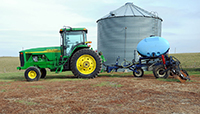 This tractor is towing an applicator, which allows fertilizers to be carefully placed on fields.