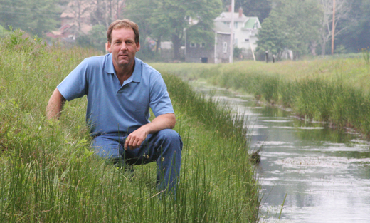 Gary Randal next to the bypass canal around his cranberry bog.