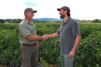 A farmer and NRCS conservationist shake hands in a field.