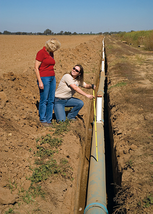 A California dairy farmer and NRCS conservationist perform a construction inspection on a newly installed irrigation pipeline.