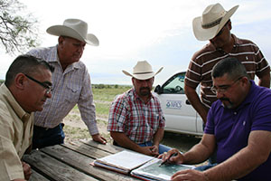 NRCS and Texas State Soil and Water Conservation Board staff discuss the Serna's conservation plan.