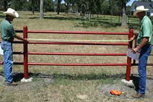 Larry Svetlik (left) and Chris Janak (right) measure the end brace of a cross fence installed for rotational grazing.
