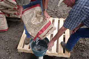 Svetlik and helper add bentonite into the casing as one part of the process to seal the well.