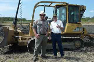 Standing in front of the bulldozer with a GPS for precision depth control of a constructed swale in the background are Jim Reed (right), owner of the Reed Family Ranch in Navarro County, and Justin Latham (left), construction foreman at L-3 Construction in Gatesville.