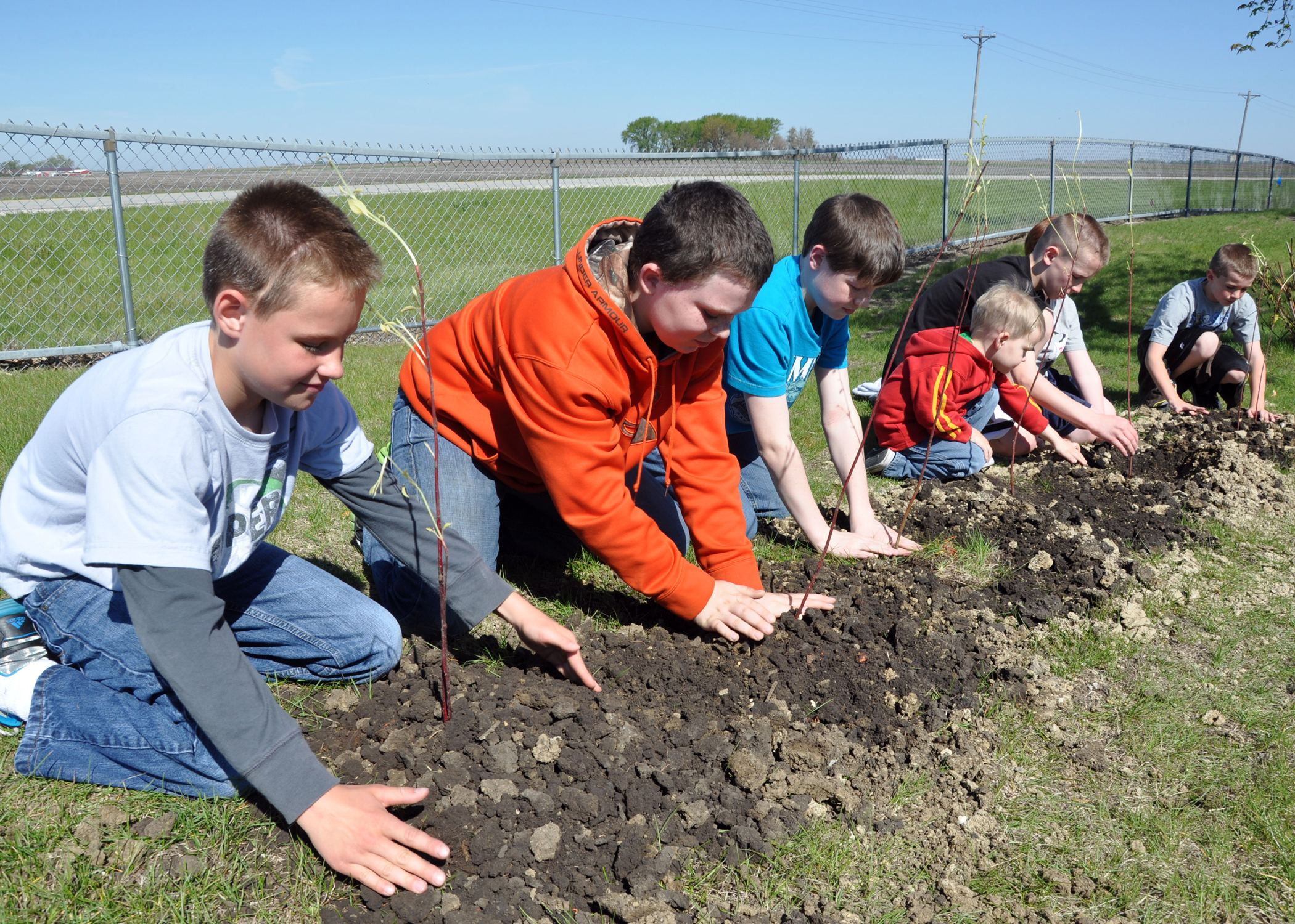 Fifth grade students from Prairie Valley School plant bushes as part of an Eath Day Project.