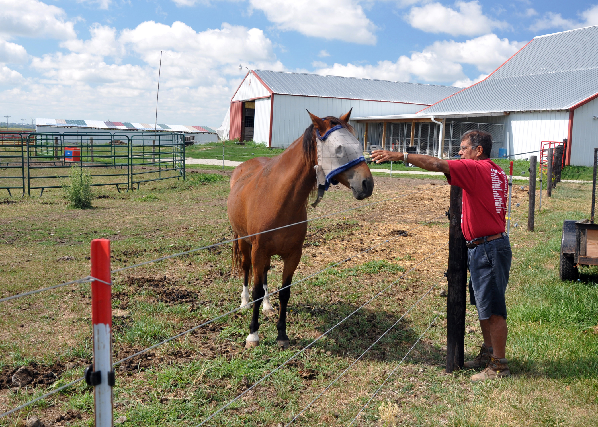 Dallas County organic farmer pets his horse. NRCS helped Garcia with a rotational grazing system.