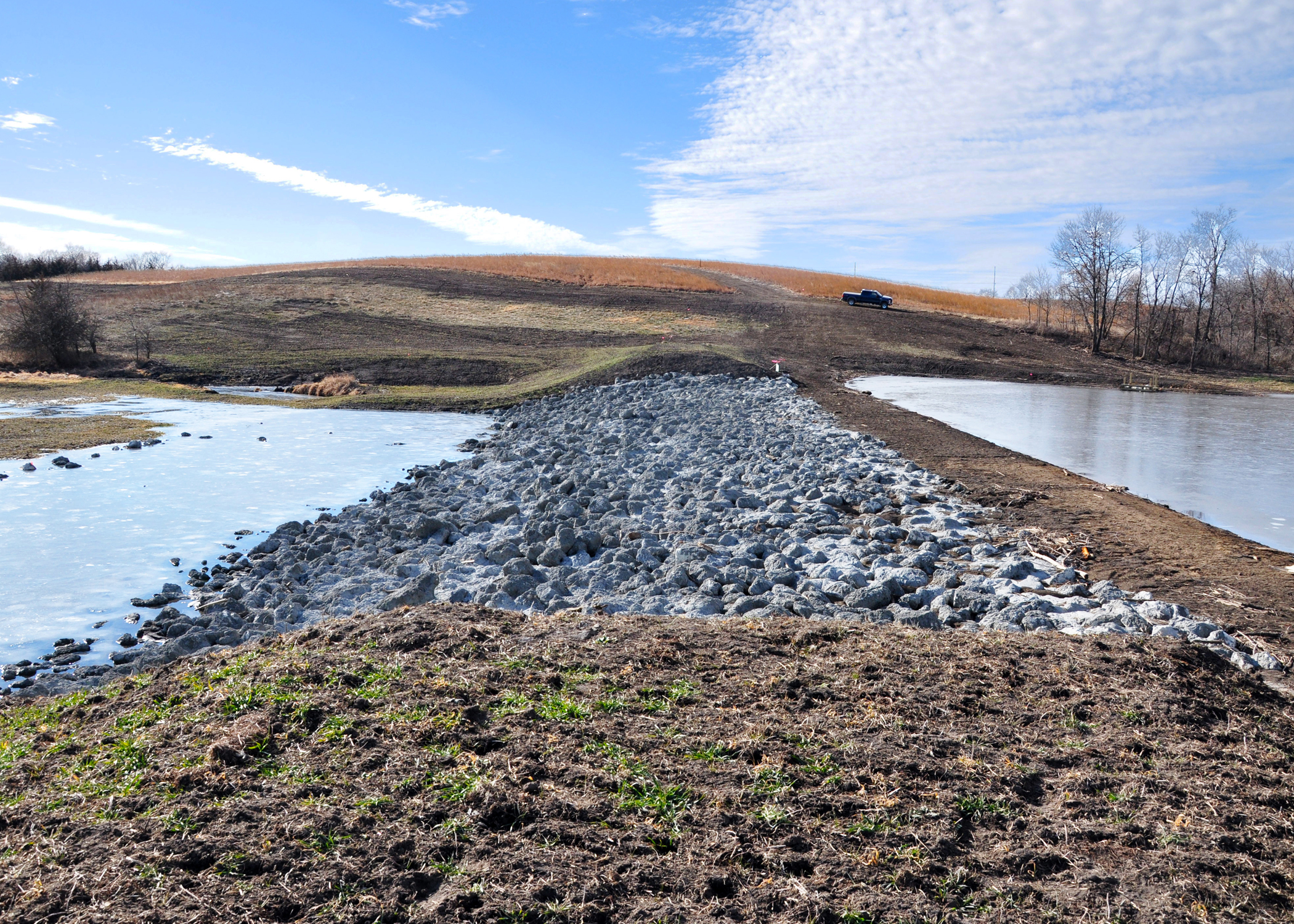 A dam and rock chute allow water to back up into the wetland (to the right), whi
