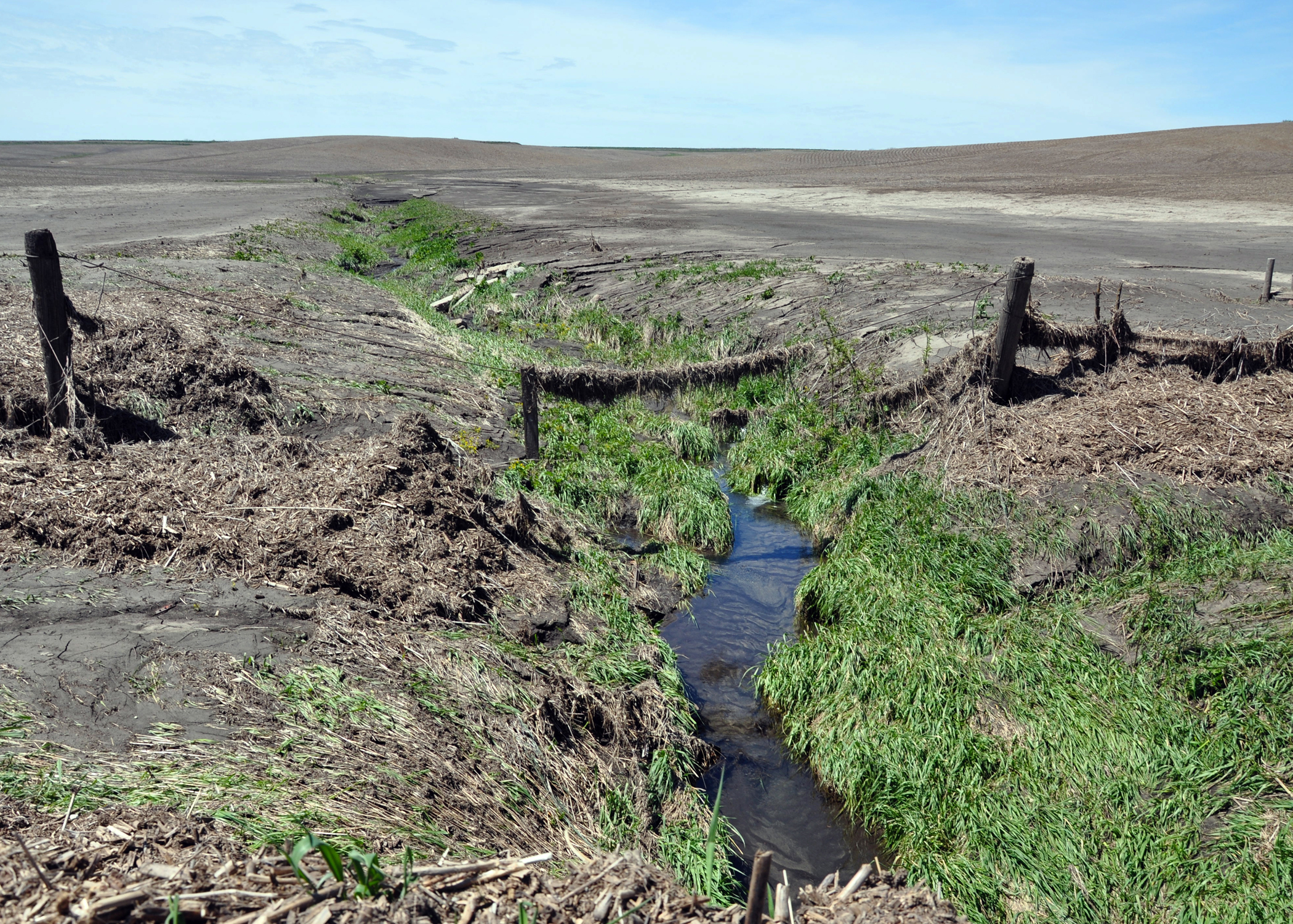 Soil erosion has created an enormous gully and damaged a fence in western Iowa.