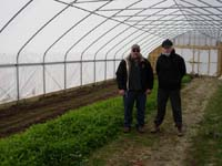 District Conservationist Tommy Wiltbank stands with Kent County producer in his high tunnel.