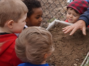 Children watching a demonstration about soil erosion