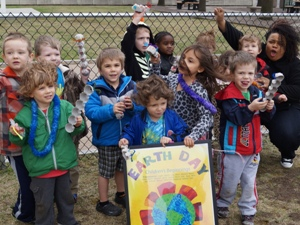 Students and their teacher pose for a group photo at an Earth Day event in Syracuse, New York