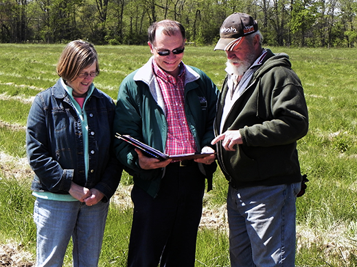 NRCS District Conservationist talks to producers Ron and Jill Osting about their conservation plan