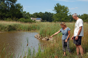 Rita Thibodeau, NRCS District Conservationist, and Peter Talmage look at the marsh created as part of his Wetlands Reserve Program project.