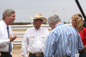 Secretary Vilsack and former Congressman Combest discuss drought conditions with the Harmons.