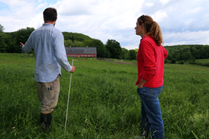A farmer and an NRCS employee discuss conservation concerns in a field.