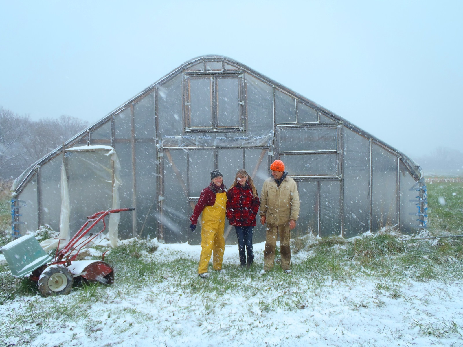 Doug and Mary Newman with their daughter outside their seasonal high tunnel