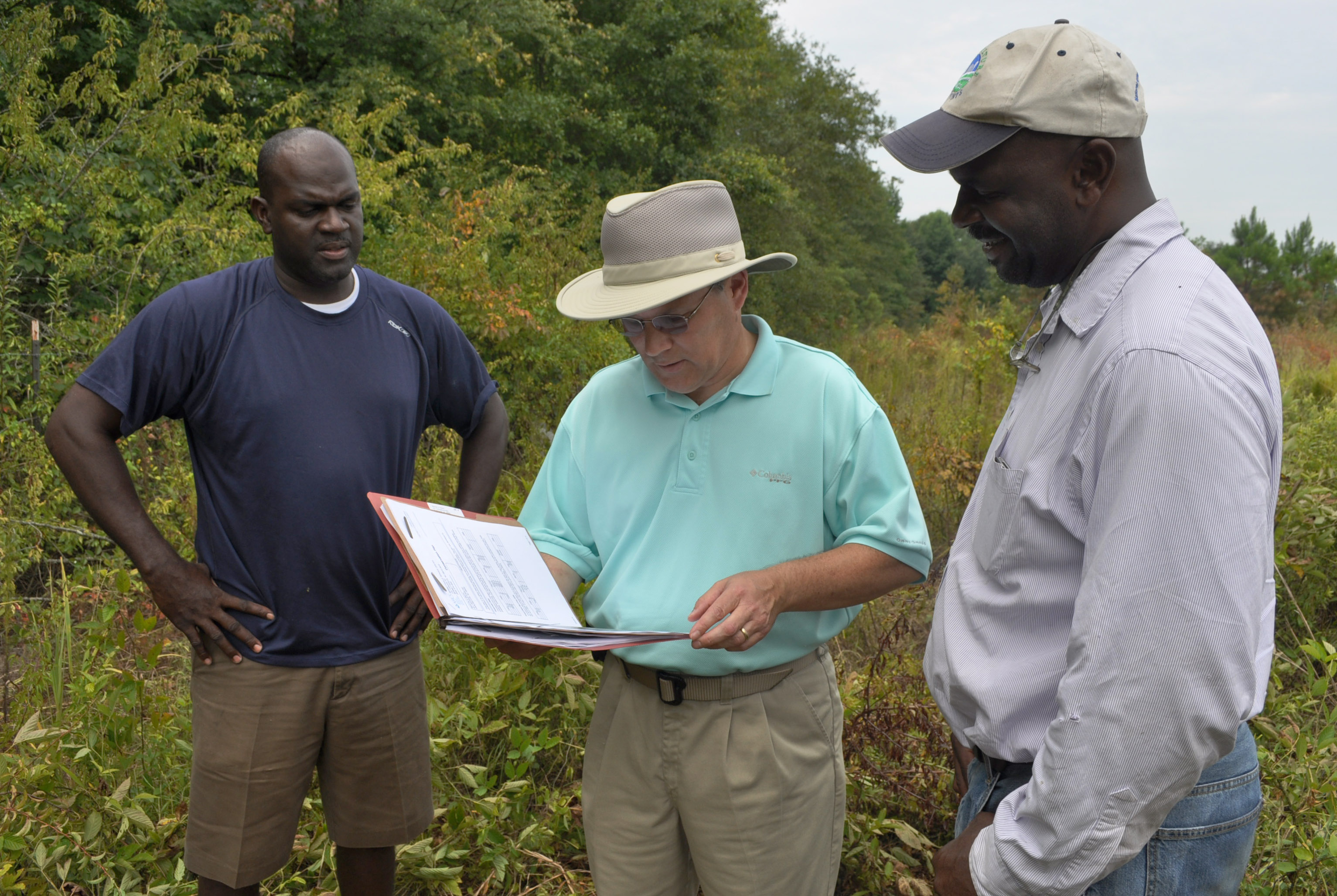 NRCS District Conservationist Frank Stephens talks with brothers Martin and Oliver Smith about their