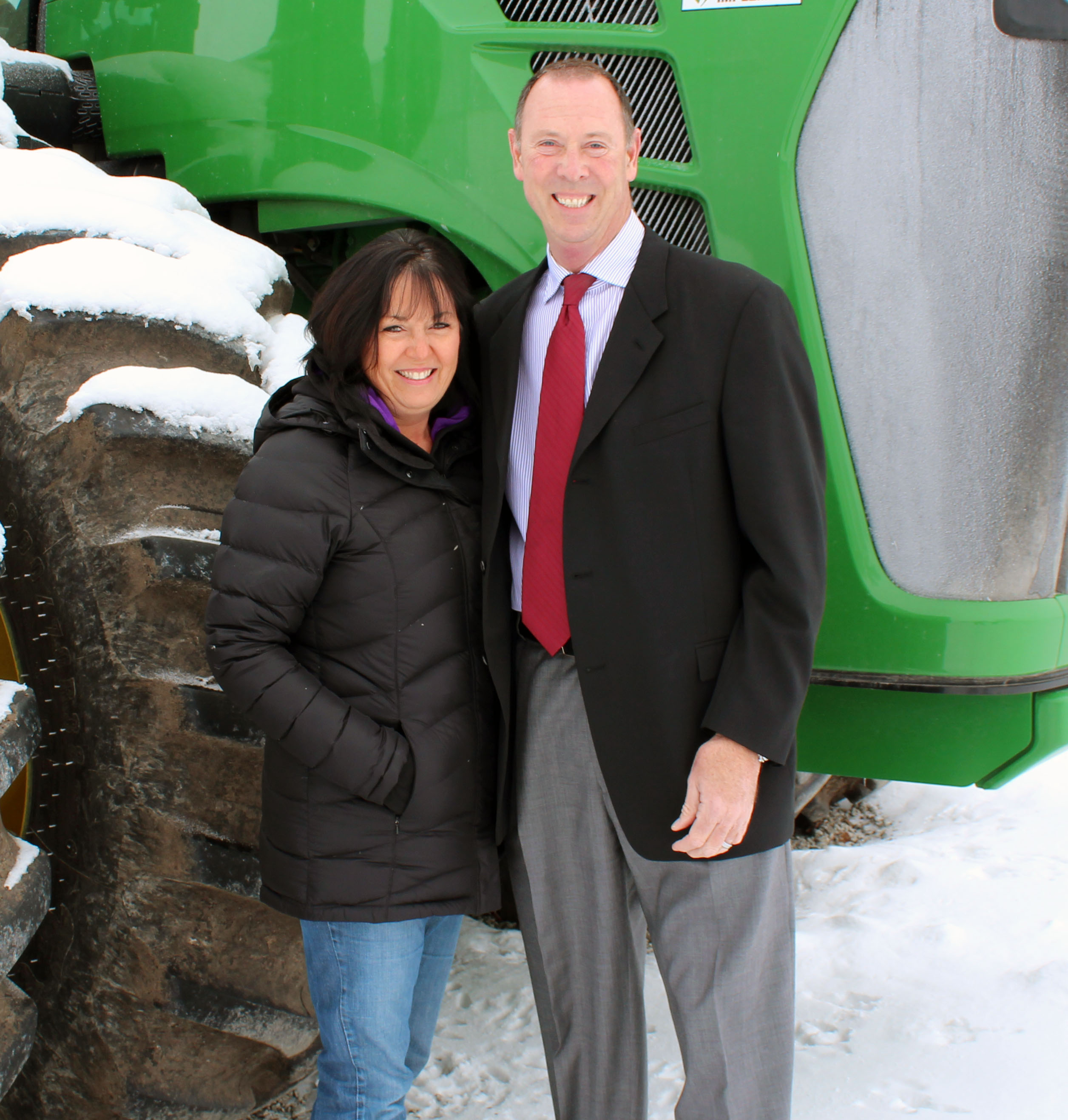 Kathy and Larry bennett standing in front of tractor