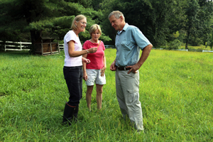 (left to right) Liz McGuire discusses grasses with Nancy and Jim Faulkner in a field on their farm.