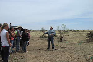 NRCS Soil Conservation Technician Gary Parks discusses the Cholla root system with students.