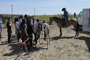 Mike Lemons explains traditional ranching tools to a group of freshman students.