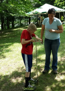 Maggie Gnann observes as a student uses a soil auger to take a soil sample