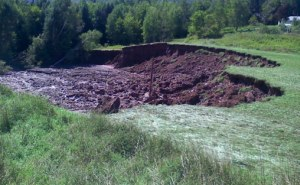 Erosion on an auxiliary spillway that occurred after a 500 year event (14 inches in 24 hours). Auxiliary spillways should not breach during a Probable Maximum Precipitation (30 inches in 24 hours) event according to NRCS criteria for high hazard dams in TR-60. Click image for full screen view