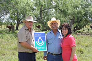 Bruce Healy presents a NRCS partner sign to Arnold and Ida Trejo for their conservation efforts.