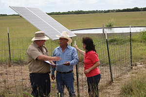 The Trejos visit with Bruce Healy about the solar pump & watering facility.