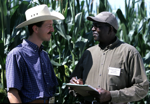NRCS - Texas staffer and a customer standing in a field discussing his conservation plan.