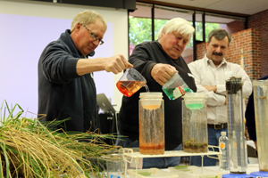 Attendees at the soil health workshop in Dighton participate in an infiltration test.
