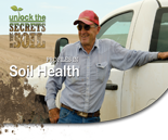 Soil Health Profiles Icon - Photo of man standing in his field in front of his truck